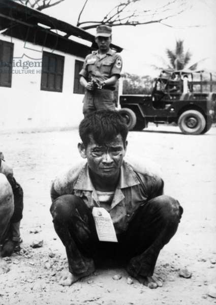 Vietnam War, Viet Cong, heavily guarded, awaits interrogation following capture in the attacks on the capital city during the festive Tet holiday period, c.late 1960s