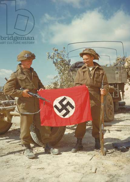 Canadian soldiers with a Nazi flag captured in Haut-Mesnil. August 10, 1944. Normandy, France, World War 2