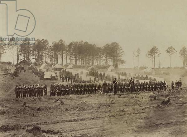 Guard mount' at Camp of 114th Pennsylvania Volunteer Infantry, Brandy Station, Virginia, Feb. 1864. They guarded the headquarters of General Meade, who shared the 114th's hometown, Philadelphia. In the background are their winter quarters, constructed with a combination of logs, rough cabins with rough chimneys of stone, bricks and barrels; all topped with tenting canvas. Photo by Alexander Gardner