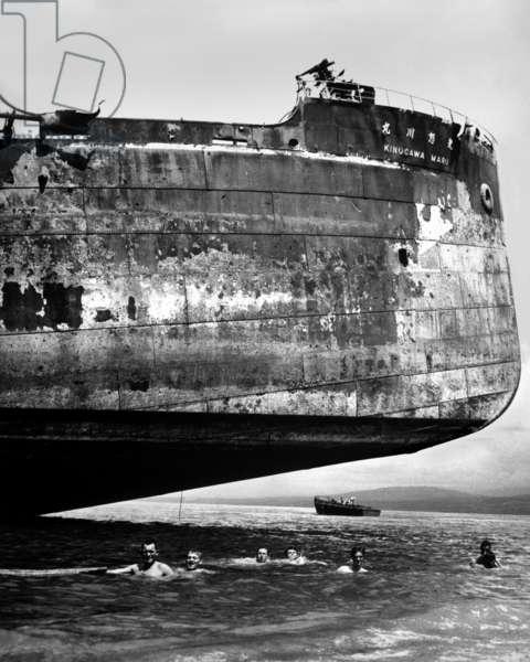 U.S. Coast Guardsmen swim near the wrecked Japanese transport, 'Kinuga Maru' at Guadalcanal. Kinugawa Maru sunk by Marine artillery and bombers from the USS Enterprise on Nov. 15, 1942