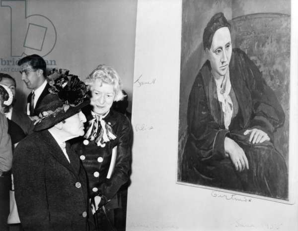 Janet Flanner (1892-1978) standing with Alice B. Toklas (1877-1967) in front of Picasso's portrait of Gertrude Stein (1874-1946). 1955. Image has fine art copyright. All uses require further clearance from artist or artist's representative