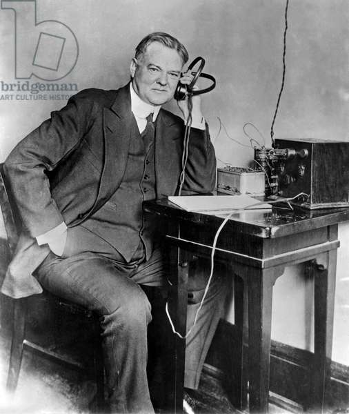 Secretary Herbert Hoover, an enthusiastic radio fan, listens in to reports of returns from the recent state primaries which so materially increased his lead in the race for the Republica nomination for president. 1928 or earlier.
