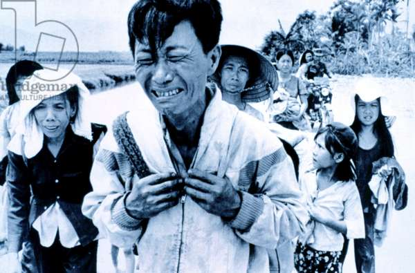 Vietnam War: A head of family weeps as his family is forced to migrate March 29, 1975