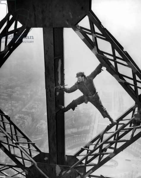 Worker painting the Eiffel Tower. Working without a safety harness he precariously straddles steel beams. The tower is being repainted in three colors: Yellow-Orange on top; Yellow -brown in the middle; and dark yellow at bottom. March 28, 1953