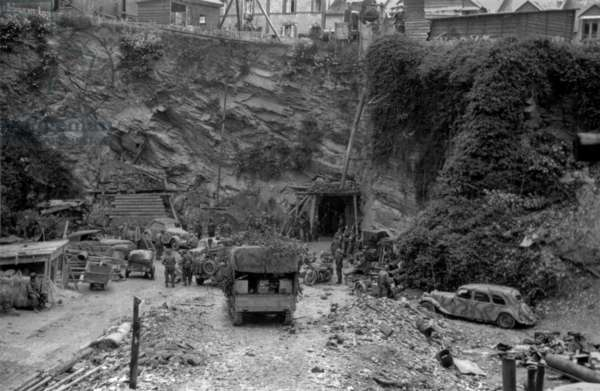 German garrison of Cherbourg surrenders on June 26, 1944. Photo shows U.S. and German soldiers at the entrance to the underground quarry that served as the Germans' bunker during the Battle of Cherbourg. Normandy, France, World War 2