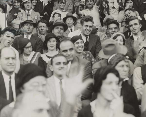 Al Capone (center), seated in front of three women, watching a college football game. He sits with other fans at the game between Northwestern and Nebraska at Dyche Stadium in Evanston, IL. Oct. 3, 1931.