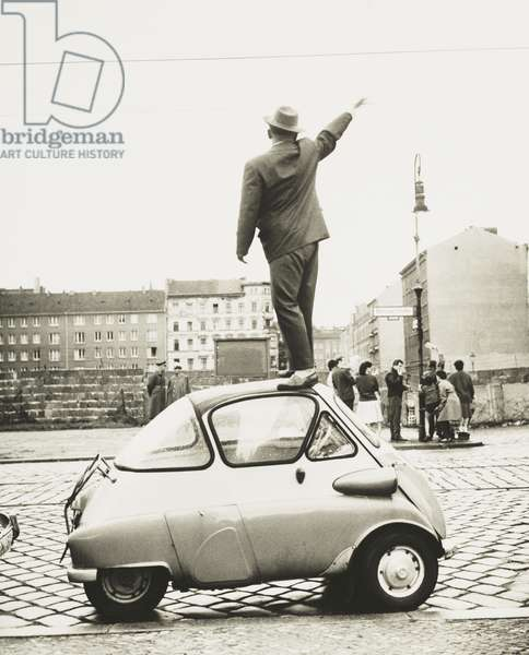 A man standing on top of a small three-wheeled car waving across the newly constructed Berlin Wall. This West Berliner waves to East Berliners on Sept. 8, 1961 on Bernauer Strasse which runs parallel to the wall