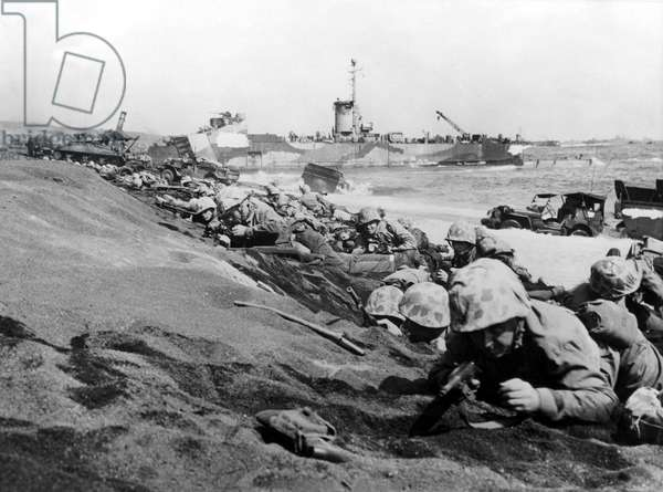IWO JIMA--Marines of the Fourth Division pinned down by enemy fire as they hit the beach at Iwo Jima on D-Day. 2/27/45.
