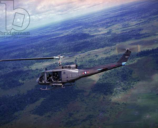Vietnam War, side view of a Vietnamese Air Force UH-1H helicopter in flight over Southeast Asia, c.late 1960s