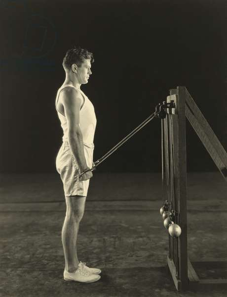 Gene Tunney, World Heavy Weight Champion lifting weights on pulleys. c. 1926