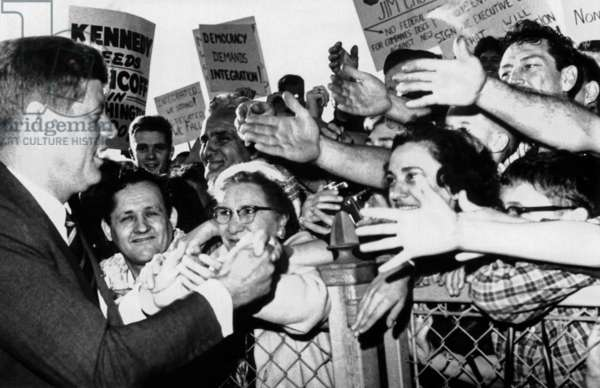 President John Kennedy greets well-wishers. JFK shakes hands at the Bridgeport, Connecticut airport while campaigning for Democratic candidates in the mid-term election. Oct. 17, 1962