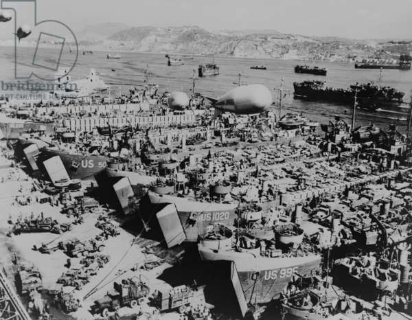 Allied invasion ships in a southern Italian port being loaded with vehicles and supplies. They will assault on the southern coast of France, in Operation Dragoon on August 15, 1944. Protective as barrage balloons hover above the anchorage. World War 2