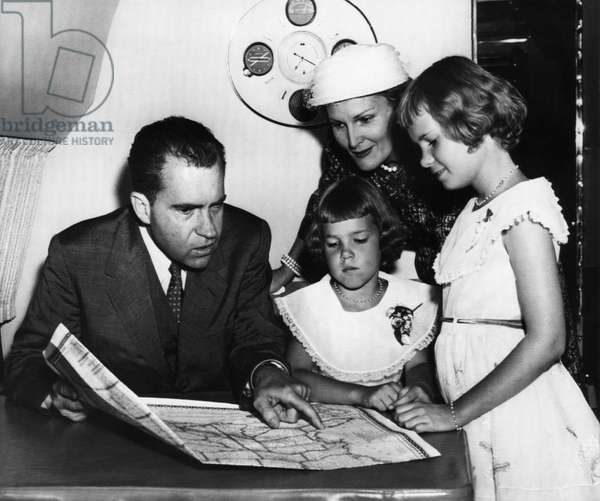 1956 US Presidency, Nixon Family. From left: Vice President (and future US President) Richard Nixon, Julie Nixon, Second Lady (and future First Lady) Patricia Nixon, Tricia Nixon. Richard Nixon shows his daughters he and Mrs. Nixon will be traveling on official business, 1956