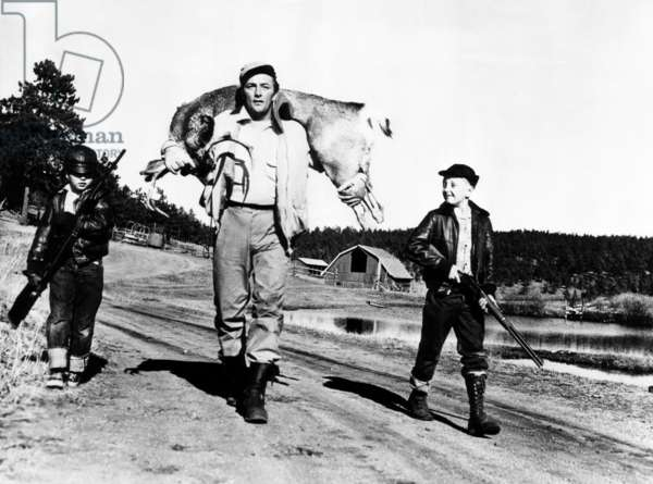 Robert Mitchum (center), and his sons, Chris Mitchum (left), and Jim Mitchum (right), after hunting a six-point buck, c.1952