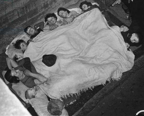 World War 2, Battle of Britain. A woman and eight children share a blanket in a southeast London subway station bomb shell during the Blitz. c. 1940-41