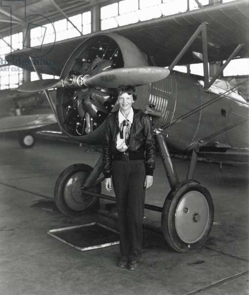 Amelia Earhart standing next to an airplane, July 30, 1936