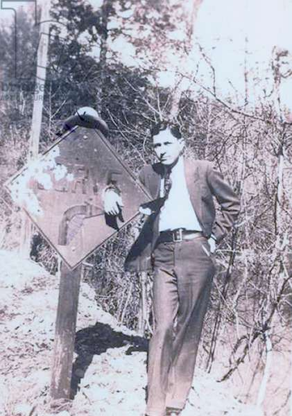 Clyde Barrow (1909-1934) dressed in a suit and standing with his hand place through a hold on a road sign