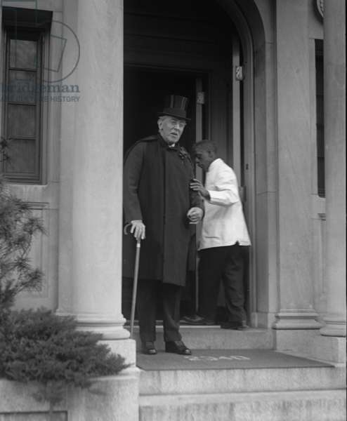 Ex-President Woodrow Wilson (1856-1924), weakened by a severe stroke in 1919, is supported by an African American servant, as he stands in the doorway of his home on his 65th birthday, Dec., 28, 1921