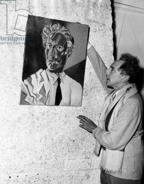 Jean Cocteau adjusts his self-portrait at an exhibition in Nice, France, 1953