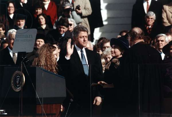 Bill Clinton (center), taking the oath of office of President of the United States, daughter Chelsea Clinton stands at front left, wife Hillary Rodham Clinton stands front, second from right, January 20, 1993