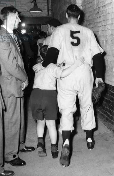 Joe DiMaggio and his son walk to the locker room after the New York Yankees' victory in the World Series, 1949