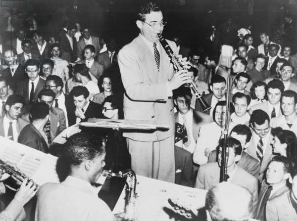 Benny Goodman (1909-86), playing clarinet, admirers look and listen. Goodman's Swing dance music was so loved, the dancers stopped to concentrate on the music. 1938