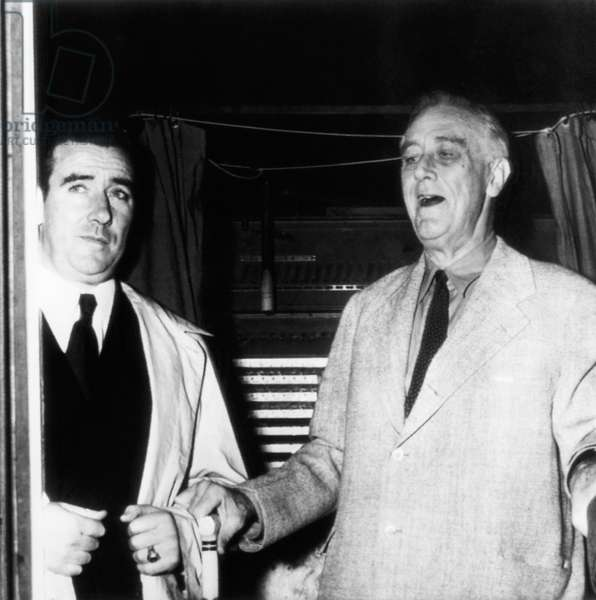 President Franklin D. Roosevelt (right), emerging from a voting booth, with a Secret Service aid, November, 1944
