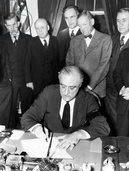 President Franklin D. Roosevelt (front), signing the declaration of war against Japan, one day after the attack on Pearl Harbor, December 8, 1941