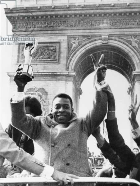 Brazilian soccer star Pele waves the Jules Rimet Cup from an open car on Paris' Champs Elysees. March 30, 1971. In the background is the Arc de Triomphe. Pele played a friendly soccer match at which Bridget Bardot blew the opening whistle and the Foreign Legion provided the band