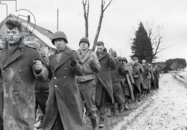 American prisoners of war are marched along a road during the Battle of the Bulge. Still from a captured German film. c. Dec. 10-17, 1944. World War 2