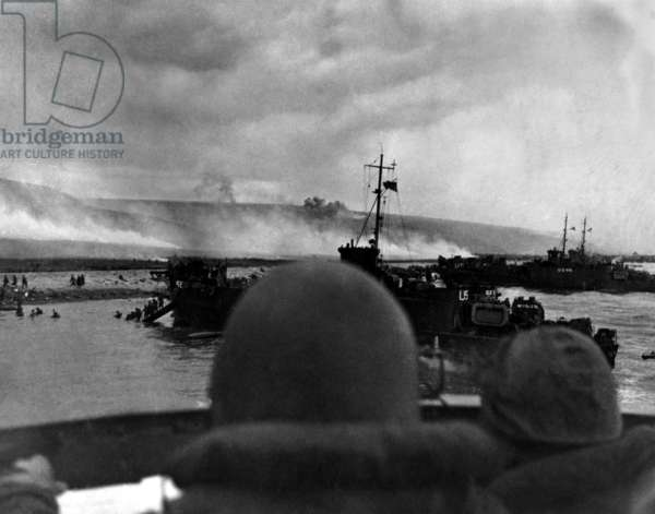 Silhouetted by helmets, view shows two landing craft at Omaha beach on D-Day. Each large ship landed 200 soldiers. June 6, 1944, World War 2