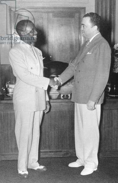 FBI Director J. Edgar Hoover shakes hands with actor/dancer Bill 'Bojangles' Robinson. Aug. 19, 1937