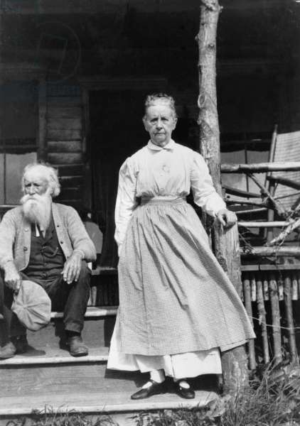 John Burroughs (1837-1921), American naturalist author seated on steps of house with his wife standing. 1915