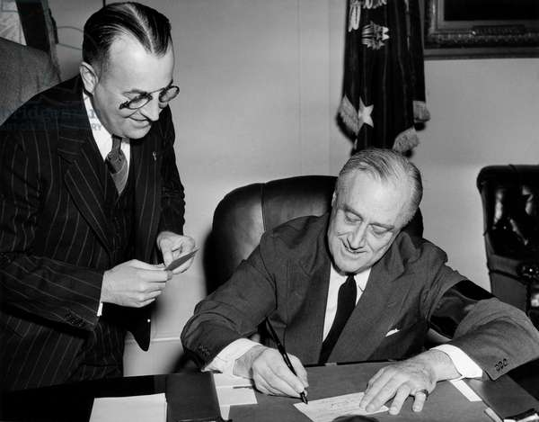 President Franklin D. Roosevelt (right), registering for the draft, at left is James D. Hayes, Chairman of the Draft Board, May, 1942
