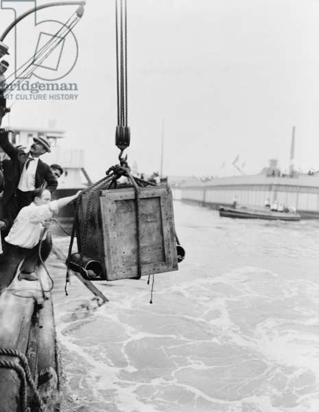 Harry Houdini (1874-1926) in the crate being lowered from ship into water in New York harbor, c. 1914
