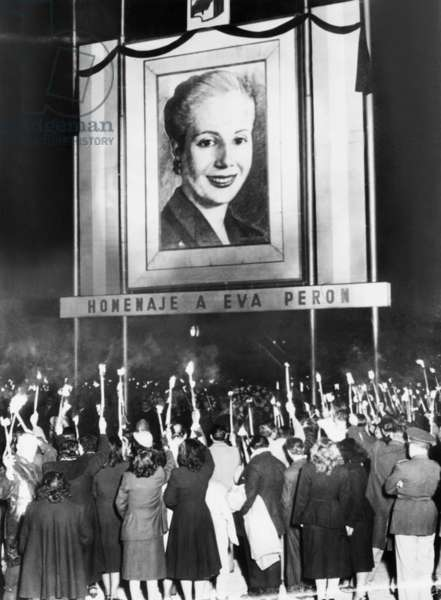 Honor Eva Peron. Argentines mourning the death of Eva Peron beneath a huge portrait of the deceased wife of their nation's President, Juan Peron. Many are holding lighted 'candle' torches. Aug. 2, 1952.