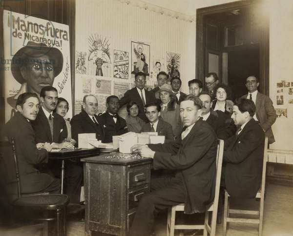 Youth Communist League with members of the 'Manos fuera de Nicaragua! Committee' (Hands Off Nicaragua Committee), sitting around a desk in 1928. General Cesar Augusto Sandino, was a rebel leader in Nicaragua, 1926-34, who resisted the US military occupation allegedly protecting American lives and interests. Sandino was assassinated in 1934 by National Guard forces of Gen. Anastasio Somoza, US client when he served as dictatorial president from 1937-1947 and 1950-1956. Photo by Tina Modotti