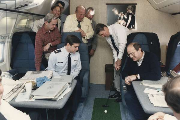 President Reagan putting a golf ball around Air Force One while flying to Geneva Summit with Soviet Union's Gorbachev. Standing to Reagan's right are George Shultz and Don Regan. November 16 1985. PO-USP-Golf-Reagan_NA-12-0097M