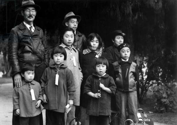 Japanese-American Mochida family wear identification tags while awaiting evacuation bus, 8th May 1942 (b/w photo)
