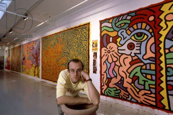 Artist Keith Haring standing in front of his paintings, c. 1985. photo by Robert Phillips / courtesy Everett Collection