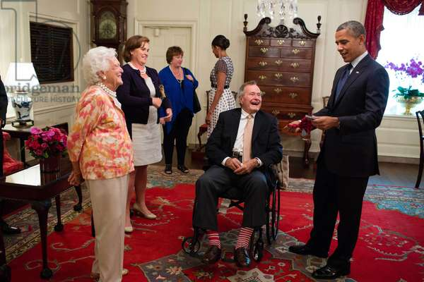 George H. W. and Barbara Bush present President Barack Obama with a pair of colorful socks. July 15, 2013. Former President Bush was attending a ceremony for the 5000th Points of Light award recipient. President Obama honored Bush41's contribution to national service