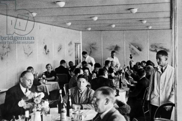 Dining 2,000 feet in the air on the Hindenburg with wine on every table. Dr. Hugo Eckener, the manager of the Luftschiffbau Zeppelin, is at the head of the Long Table. May 10, 1936.