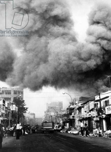 Vietnam War, black smoke over the capital city, fire trucks rush to scenes of fires set during the attacks by the Viet Cong during the Tet holiday period, Saigon, 1968