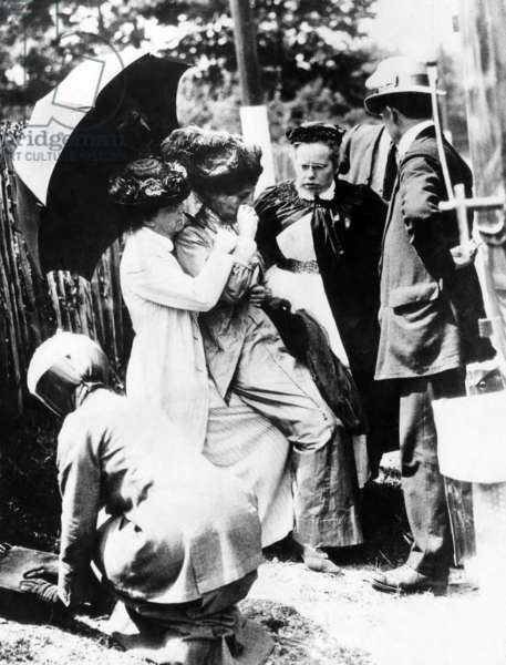 Emmeline Pankhurst (1858-1928, left of center), in a state of collapse afeter forcible feedings in jail, London, England, 1913