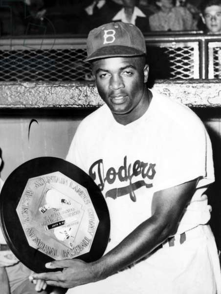 Baseball player Jackie Robinson of the Brooklyn Dodgers holds his MVP award in 1949.