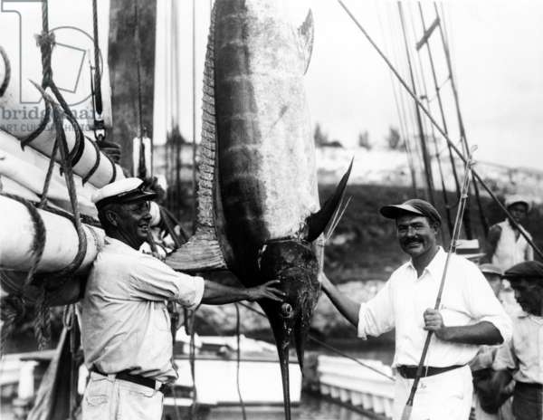 Ernest Hemingway: Ernest Hemingway (1899-1961), posed with Capt. Joe Russell of Key West, beside a huge hanging marlin they caught off the coast of Florida. Ca. 1935,