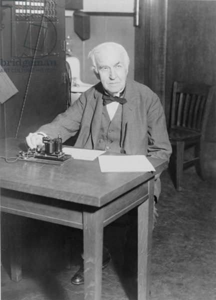 Thomas Edison, seated at desk, demonstrating an old telegraph transmitter in his West Orange, New Jersey, laboratory, 1930