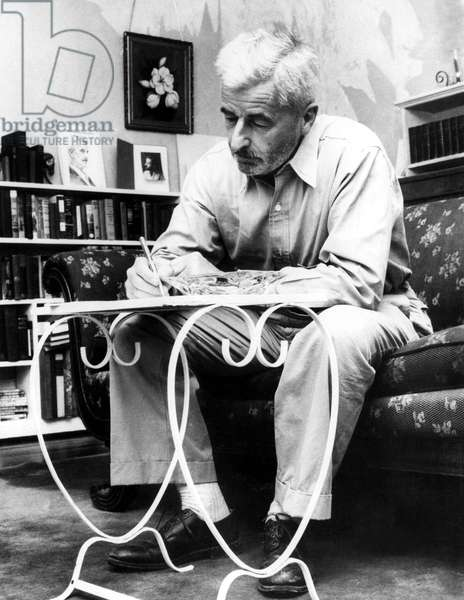 WILLIAM FAULKNER working in his home near Oxford, undated.