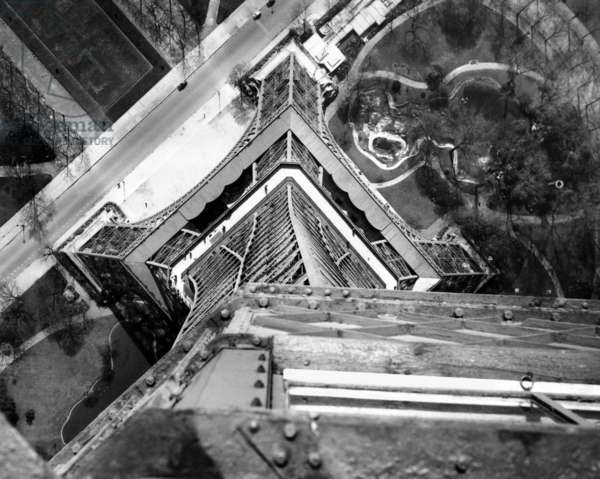 View to the ground from the heights of the Eiffel Tower. Looking down from the third platform shows a maze of steel and the Champ de Mars Gardens. April 16, 1951