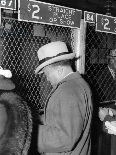 J. Edgar Hoover placing a bet at the two dollar window. It was opening day at Bowie race track, Maryland, April 1, 1938